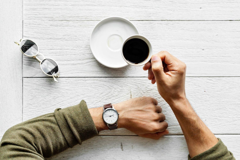 Man met horloge en kopje koffie