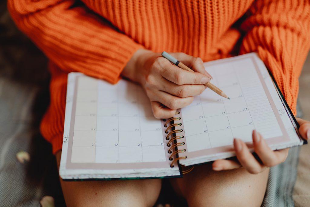 Vrouw schrijft in agenda planner