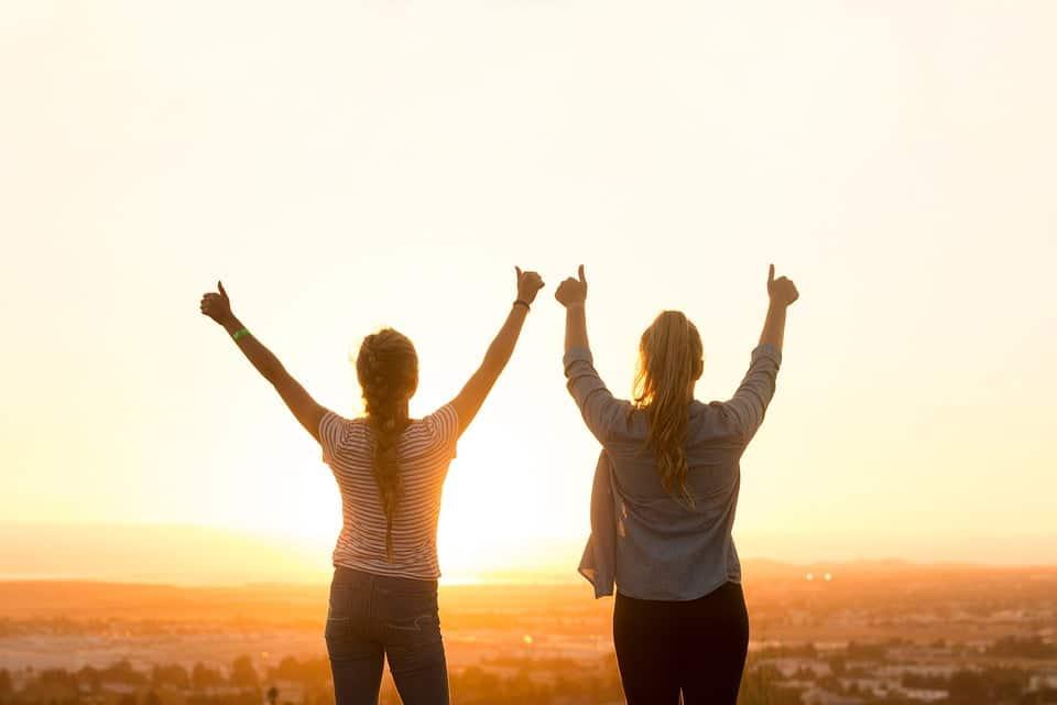 Twee dames bij zonsondergang met duim omhoog
