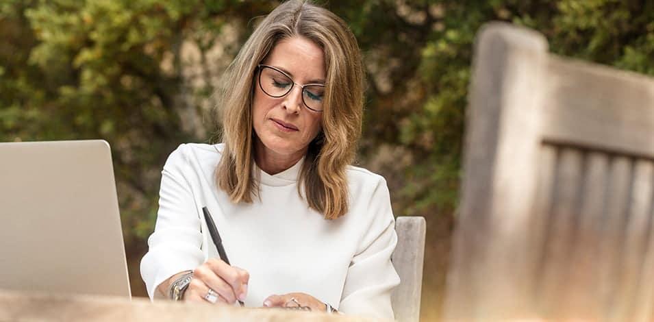 Vrouw schrijft aan tuintafel