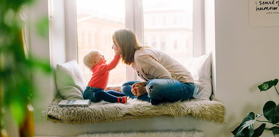 onbezorgde moeder met kind in raamkozijn
