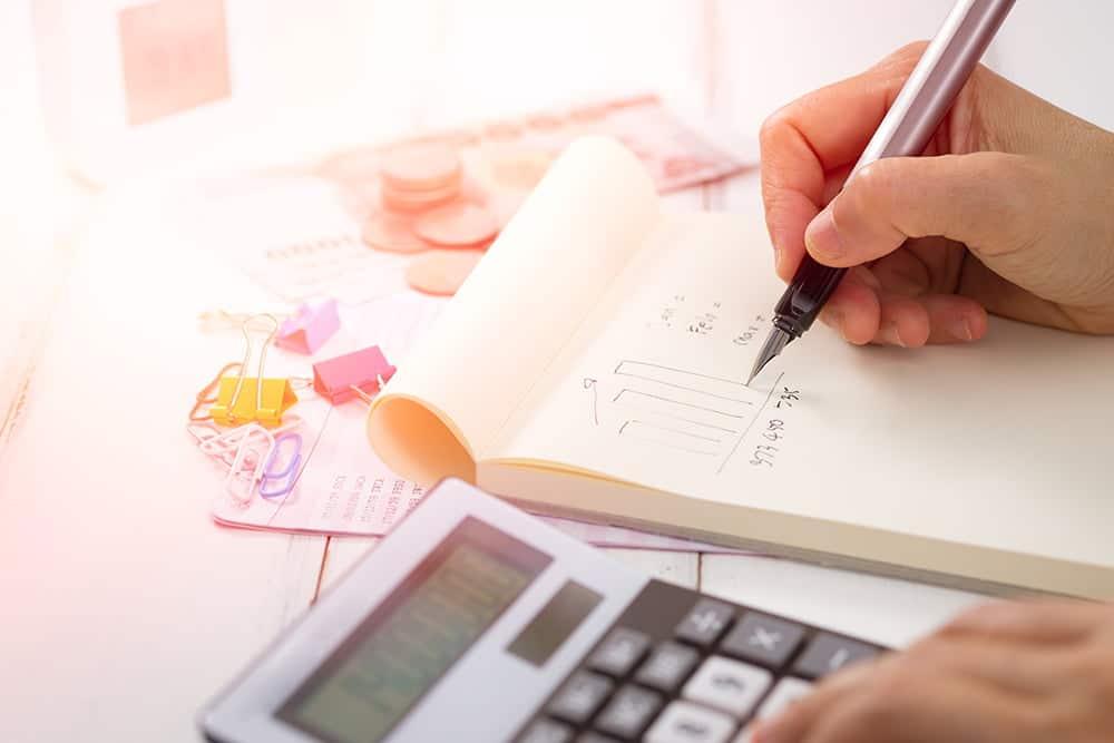 persoon met rekenmachine en geld op tafel